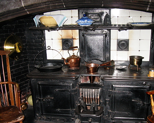 vintage kitchen image with cast iron range and copper pans