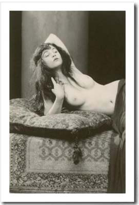 black and white vintage nude photo of a woman with pillow and rug